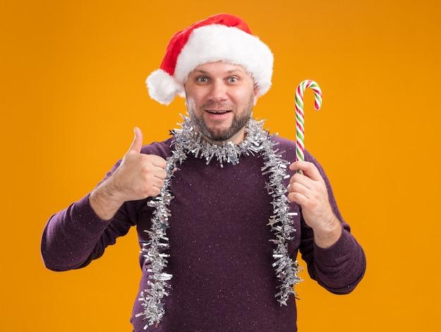 Beeindruckter mann mittleren alters, der weihnachtsmannmütze und lametta-girlande um den hals hält, der weihnachtliches süßes rohr hält, das kamera betrachtet daumen oben auf orange hintergrund lokalisiert