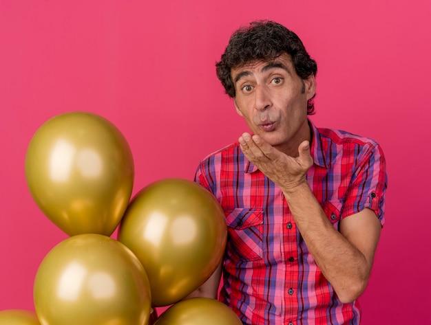 Beeindruckter party-mann mittleren alters, der luftballons hält, die nach vorne schauen und schlagkuss lokal auf purpurroter wand senden
