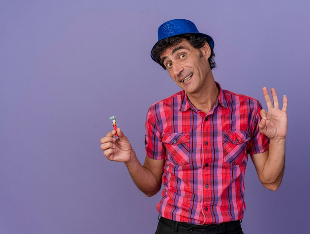 Beeindruckter party-mann mittleren alters, der partyhut hält, der partygebläse hält, das vorne tut, ok zeichen lokalisiert auf lila wand