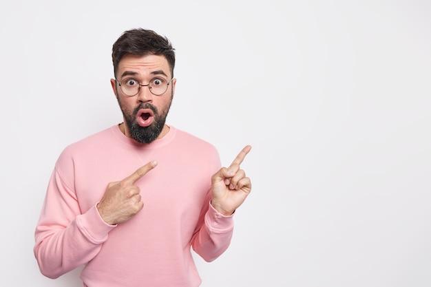 Beeindruckter schockierter europäischer mann, der mit überraschtem ausdruck auf kopienraum zeigt