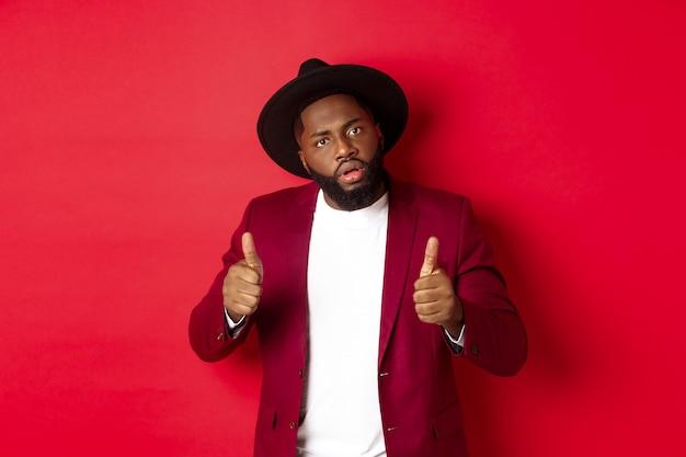 Beeindruckter schwarzer mann, der gute arbeit sagt, mit daumen hoch aufmuntern, etwas loben, vor rotem hintergrund stehen