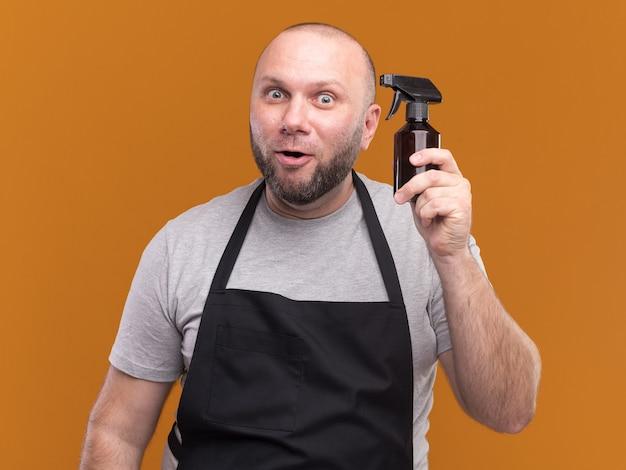 Beeindruckter slawischer männlicher friseur mittleren alters in uniform, die wassersprühflasche hält, isoliert auf orange wand