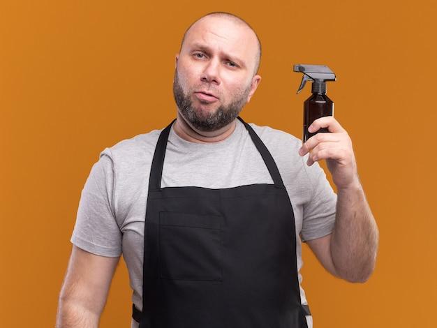 Beeindruckter slawischer männlicher friseur mittleren alters in uniform, die wassersprühflasche hält, lokalisiert auf orange wand