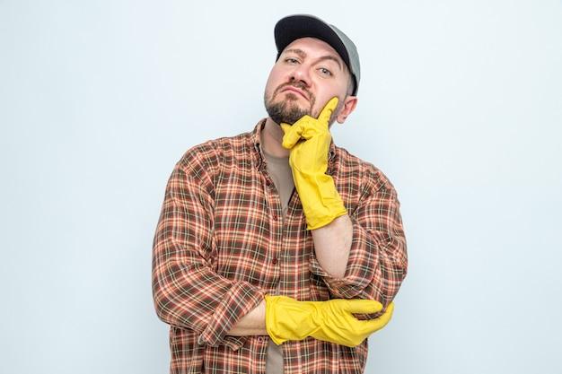 Beeindruckter slawischer putzmann mit gummihandschuhen, der die hand auf sein kinn legt und