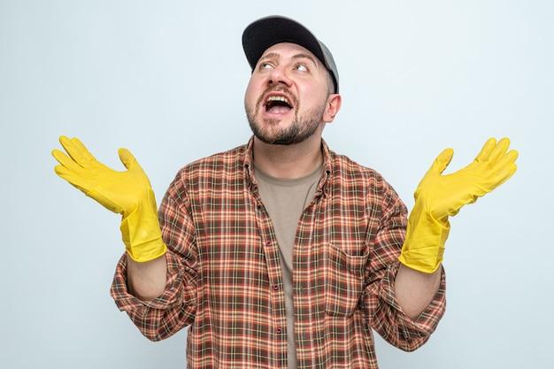 Beeindruckter slawischer putzmann mit gummihandschuhen, die die hände offen halten und nach oben schauen