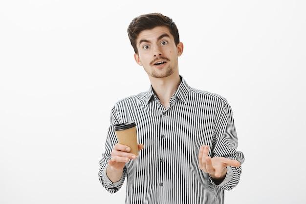 Beeindruckter typ, der nach dem besuch eines großartigen meetings gedanken mit einem freund teilt. neugierig gut aussehendes männliches model mit schnurrbart und bart, das während des gesprächs zeigt und kaffee im café trinkt