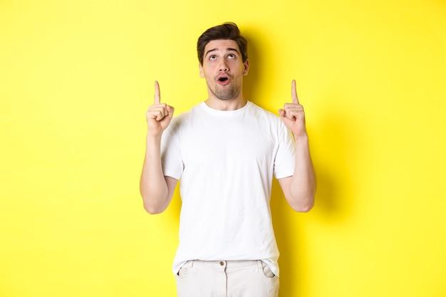 Beeindruckter typ, der sich das promo-angebot ansieht und mit dem finger auf die werbung zeigt, die über ...