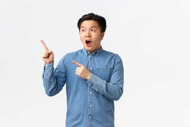 Beeindruckter und erstaunter junger asiatischer mann reagiert auf fantastische nachrichten, offener mund fasziniert, zeigt und schaut auf die obere linke ecke erstaunliches werbebanner, stehender weißer hintergrund.