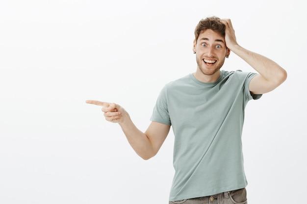 Beeindruckter und faszinierter freund, der aufgeregt und glücklich ist, mit dem zeigefinger nach links zeigt und die hand auf dem kopf hält und breit lächelt