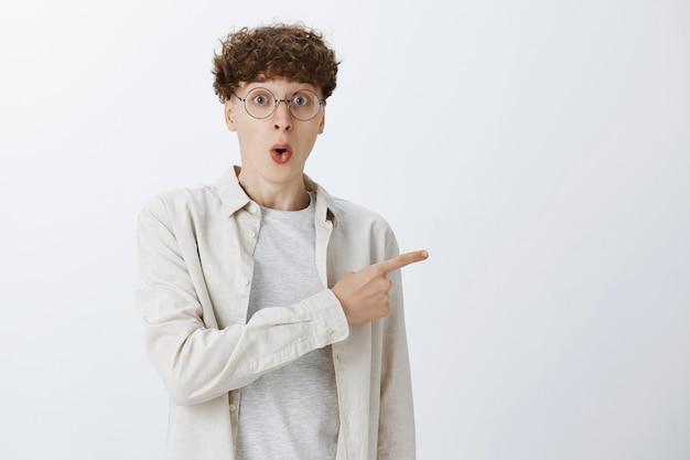 Beeindruckter und überraschter teenager, der an der weißen wand posiert