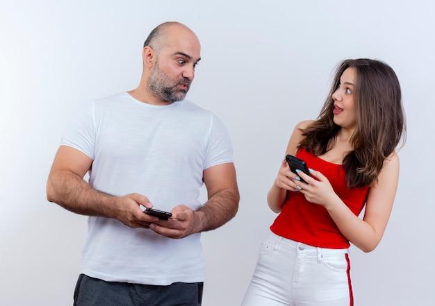 Beeindrucktes erwachsenes paar, das beide handys hält und sich ansieht