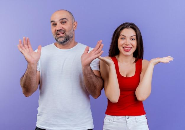 Beeindrucktes erwachsenes paar, das leere hände zeigt