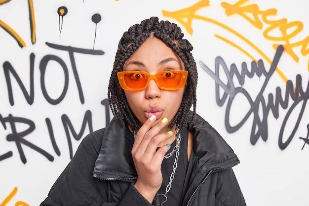 Beeindrucktes hipster-teenager-mädchen mit dreadlocks sieht sprachlos aus, wenn die kamera die hand auf den gefalteten lippen hält. sie trägt eine trendige orangefarbene sonnenbrille und eine schwarze jacke posiert an der graffiti-wand