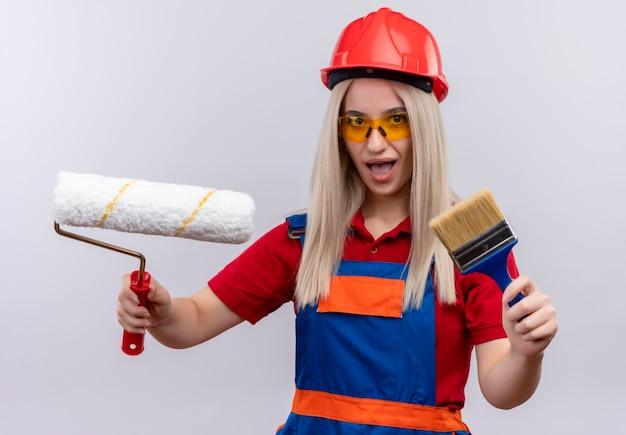 Beeindrucktes junges blondes ingenieur-baumeistermädchen in der uniform, die schutzbrille hält, die pinsel und walze auf lokalisiertem weißem raum hält