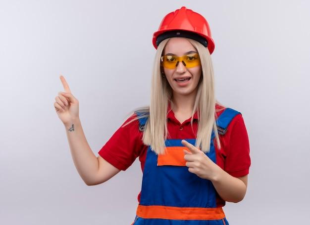 Beeindrucktes junges blondes ingenieur-baumeistermädchen in uniform in zahnspangen, die eine schutzbrille tragen, die auf der linken seite auf isolierten weißen raum zeigt