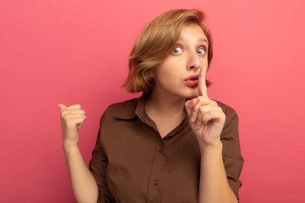 Beeindrucktes junges blondes mädchen, das stille geste macht, die hinter isoliert auf rosa wand zeigt