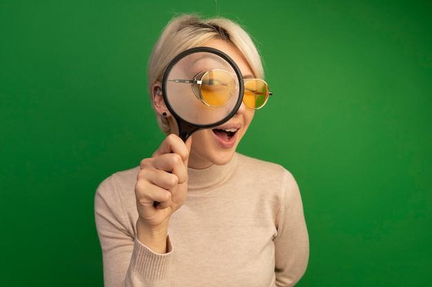 Beeindrucktes junges blondes mädchen mit sonnenbrille, das eine lupe durch sie hält