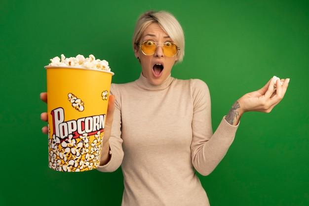 Beeindrucktes junges blondes mädchen mit sonnenbrille, das einen eimer popcorn ausstreckt und popcornstücke isoliert auf grüner wand hält