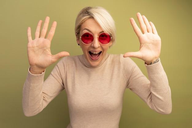 Beeindrucktes junges blondes mädchen mit sonnenbrille, das leere hände zeigt