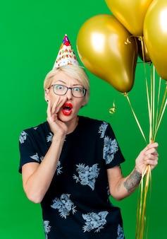 Beeindrucktes junges blondes partygirl, das brille und geburtstagskappe hält, die ballons hält, die kamera betrachten und lokalisiert auf grünem hintergrund flüstern