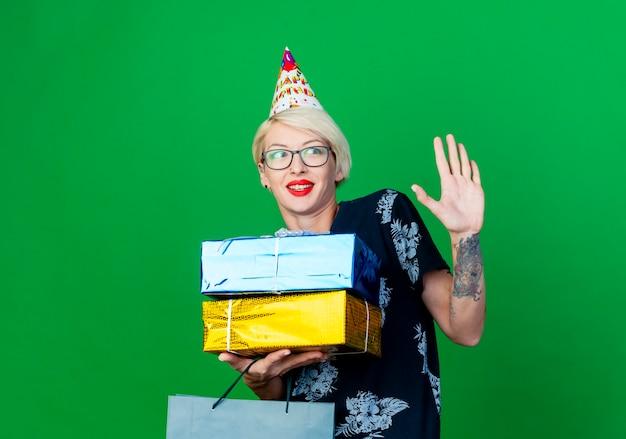 Beeindrucktes junges blondes partygirl, das brille und geburtstagskappe trägt, die seite betrachtet, die papiertüte und geschenkboxen lächelnd und keine geste lokalisiert auf grünem hintergrund mit kopienraum tut
