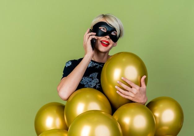 Beeindrucktes junges blondes partygirl, das maskerademaske trägt, die hinter luftballons steht, die einen von ihnen betrachten, die seite betrachten, die am telefon lokalisiert auf olivgrünem hintergrund spricht