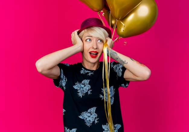 Beeindrucktes junges blondes partygirl, das partyhut hält, das ballons hält, die hände auf kopf setzen, die seite lokal auf purpurrotem hintergrund betrachten