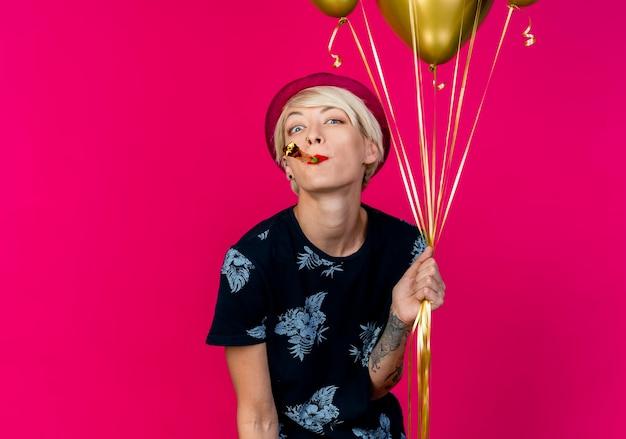 Beeindrucktes junges blondes partygirl, das partyhut hält, der ballons und partygebläse im mund hält, das kamera betrachtet, das partybläser auf purpurrotem hintergrund mit kopienraum bläst