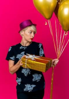 Beeindrucktes junges blondes partygirl, das partyhut hält, der geschenkbox und luftballons hält, die seite lokal auf purpurrotem hintergrund betrachten
