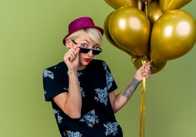 Beeindrucktes junges blondes partygirl, das partyhut und sonnenbrille hält, die luftballons hält und die gläser betrachten, die kamera lokalisiert auf olivgrünem hintergrund mit kopienraum betrachten