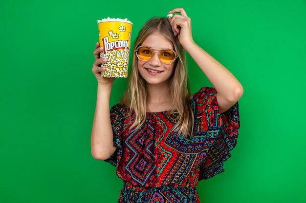 Beeindrucktes junges blondes slawisches mädchen mit sonnenbrille, das popcorn-eimer hält und