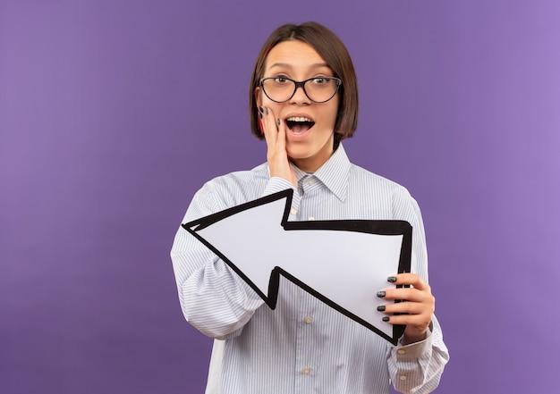 Beeindrucktes junges callcenter-mädchen, das eine brille trägt, die hand auf gesicht setzt und pfeilmarkierung hält, die auf seite zeigt, die auf purpur mit kopienraum lokalisiert ist