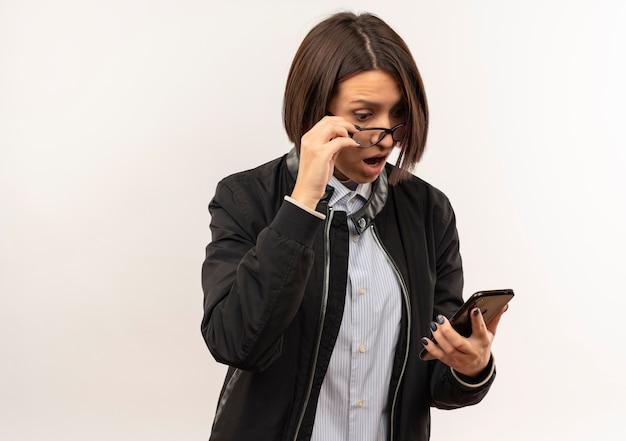 Beeindrucktes junges callcenter-mädchen, das eine brille trägt, die ihre brille und ihr mobiltelefon hält und das telefon lokalisiert auf weiß mit kopienraum betrachtet