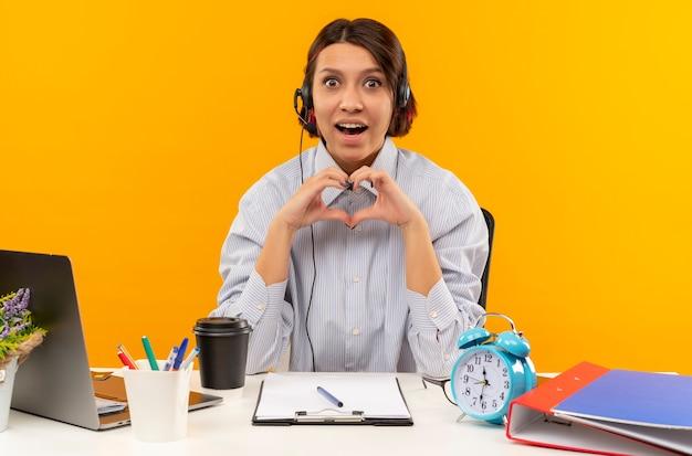 Beeindrucktes junges callcenter-mädchen, das headset am schreibtisch sitzt und herzzeichen lokalisiert auf orange trägt