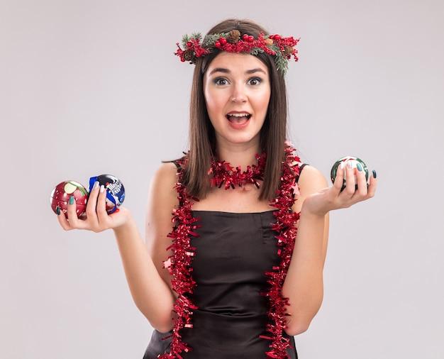Beeindrucktes junges hübsches kaukasisches mädchen, das weihnachtskopfkranz und lametta-girlande um den hals trägt und weihnachtskugeln hält und die kamera einzeln auf weißem hintergrund betrachtet looking