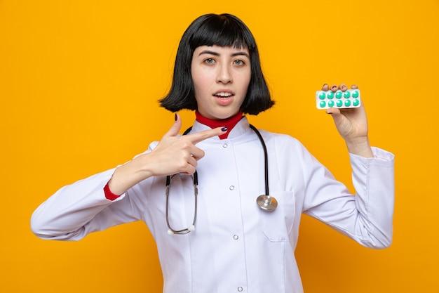 Beeindrucktes junges hübsches kaukasisches mädchen in arztuniform mit stethoskop, das auf pillenverpackungen hält und zeigt