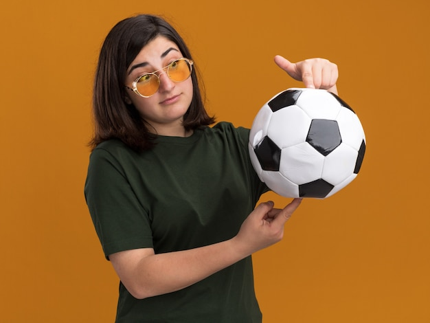 Beeindrucktes junges hübsches kaukasisches mädchen in der sonnenbrille, die ball lokalisiert auf orange wand mit kopienraum hält und betrachtet