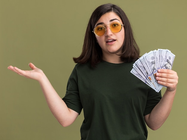 Beeindrucktes junges hübsches kaukasisches mädchen in sonnenbrille hält geld und hält hand offen auf olivgrün