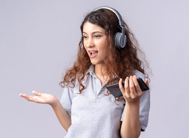 Beeindrucktes junges hübsches kaukasisches mädchen mit kopfhörern, das handy hält und auf die seite schaut, die leere hand isoliert auf weißer wand zeigt