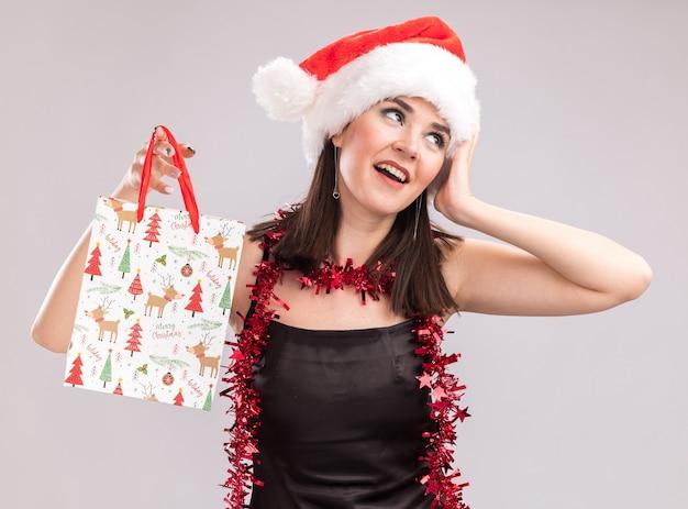 Beeindrucktes junges hübsches kaukasisches mädchen mit weihnachtsmütze und lametta-girlande um den hals, das eine weihnachtsgeschenktüte hält und den kopf berührt, der auf die seite isoliert auf weißem hintergrund schaut