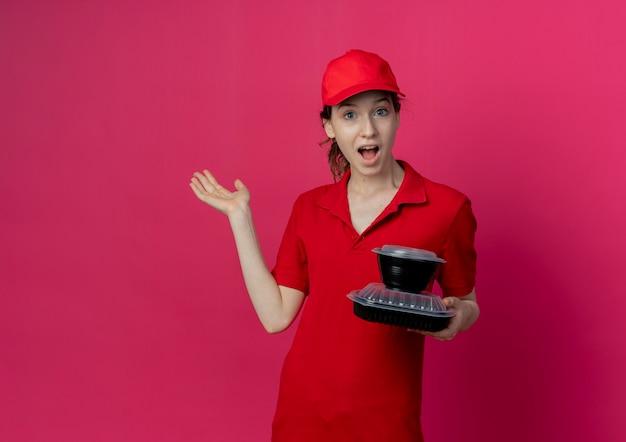 Beeindrucktes junges hübsches liefermädchen, das rote uniform und kappe hält, die lebensmittelbehälter zeigt, die leere hand lokalisiert auf purpurrotem hintergrund mit kopienraum zeigen