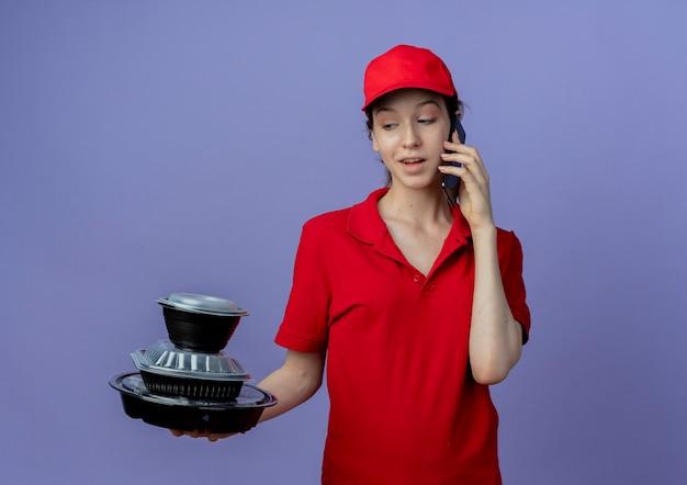 Beeindrucktes junges hübsches liefermädchen, das rote uniform und kappe hält und lebensmittelbehälter betrachtet und am telefon lokalisiert auf lila hintergrund mit kopienraum spricht