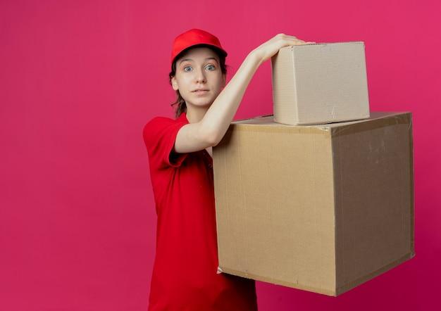 Beeindrucktes junges hübsches liefermädchen in der roten uniform und in der kappe, die kartonkästen betrachten, die kamera lokal auf purpurrotem hintergrund mit kopienraum betrachten
