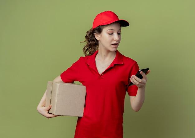 Beeindrucktes junges hübsches liefermädchen in der roten uniform und in der kappe, die kartonschachtel und handy hält, das telefon lokalisiert auf olivgrünem hintergrund mit kopienraum betrachtet