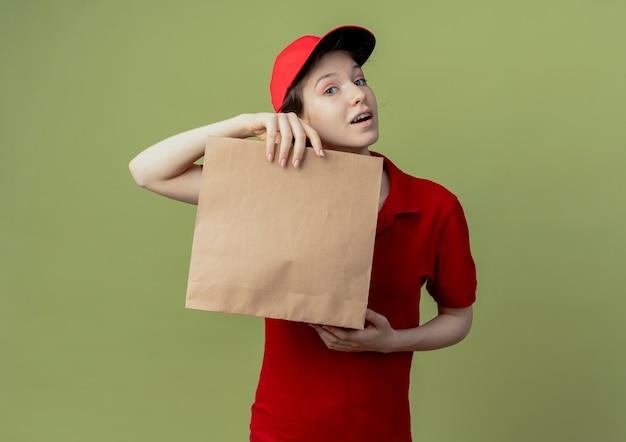 Beeindrucktes junges hübsches liefermädchen in der roten uniform und in der kappe, die papierpaket hält, das kamera lokalisiert auf olivgrünem hintergrund mit kopienraum betrachtet