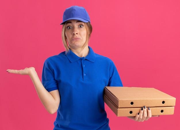 Beeindrucktes junges hübsches liefermädchen in uniform hält die hand offen und hält pizzaschachteln auf rosa