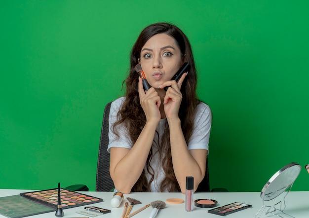 Beeindrucktes junges hübsches mädchen, das am make-up-tisch mit make-up-werkzeugen sitzt, die erröten und puderpinsel halten und gesicht mit ihnen lokalisiert auf grünem hintergrund berühren