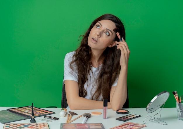 Beeindrucktes junges hübsches mädchen, das am make-up-tisch mit make-up-werkzeugen sitzt, errötenden pinsel hält und stirn damit berührt und lokalisiert auf grünem hintergrund schaut