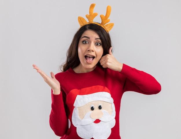 Beeindrucktes junges hübsches mädchen, das rentiergeweih-stirnband und weihnachtsmannpullover trägt und leere hand und daumen oben zeigt