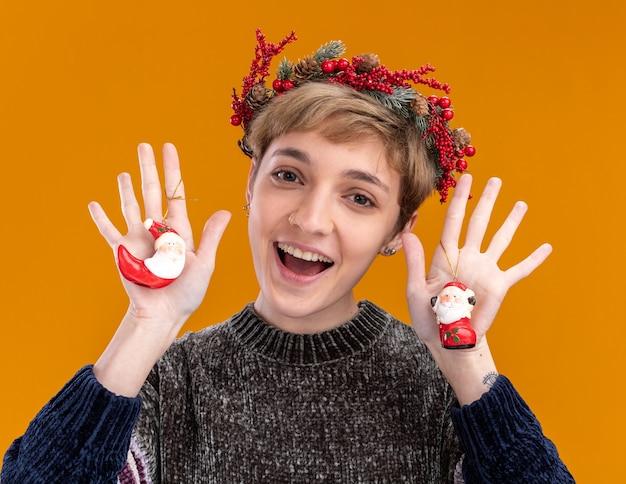 Beeindrucktes junges hübsches mädchen, das weihnachtskopfkranz hält, der weihnachtsmannverzierungen des weihnachtsmanns betrachtet, die kamera lokalisiert auf orangefarbenem hintergrund betrachten